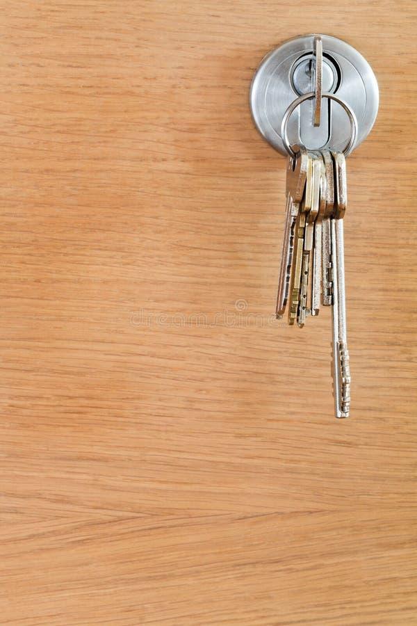 Bunch of home keys in lock of wood door. Close up stock photography