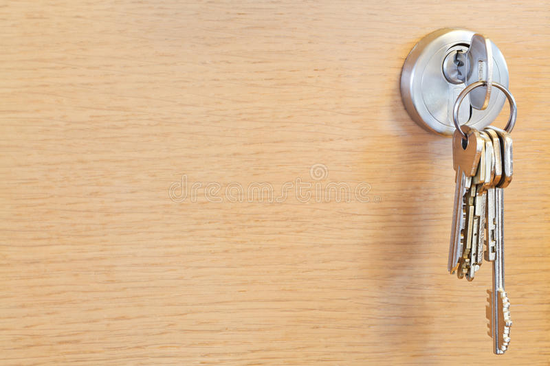 Bunch of home keys in lock of wooden door. Bunch of home keys in cylinder lock of wooden door stock image