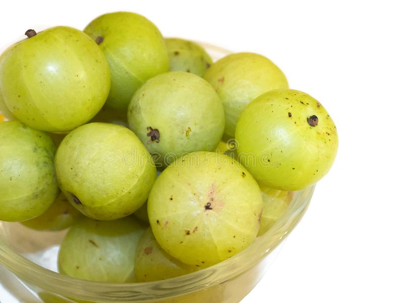 The bunch of Indian Gooseberry Phyllanthus emblica in a round glass bowl isolated on white background. royalty free stock images