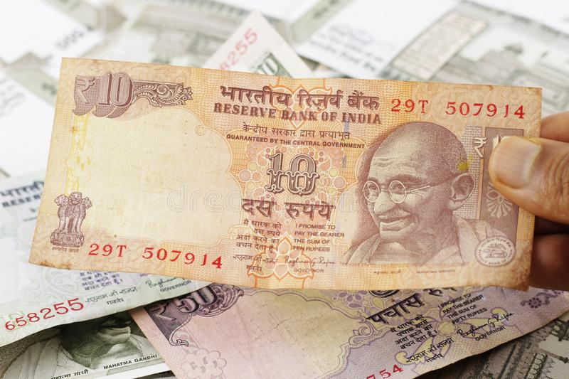 A Bunch of Indian Rupees. A Bunch of Indian currency, five hundred rupees notes spread across a surface with ten rupee note held in hand stock image