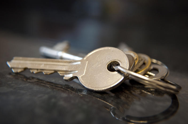 Bunch of keys. A bunch of house keys on a keyring resting on a reflective dark surface stock image
