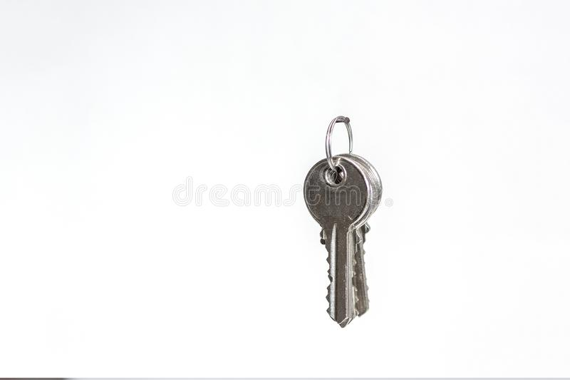 A bunch of keys hanging on a nail isolated against a white backg. A bunch of keys hanging on a carnation on a white wall in the house stock images