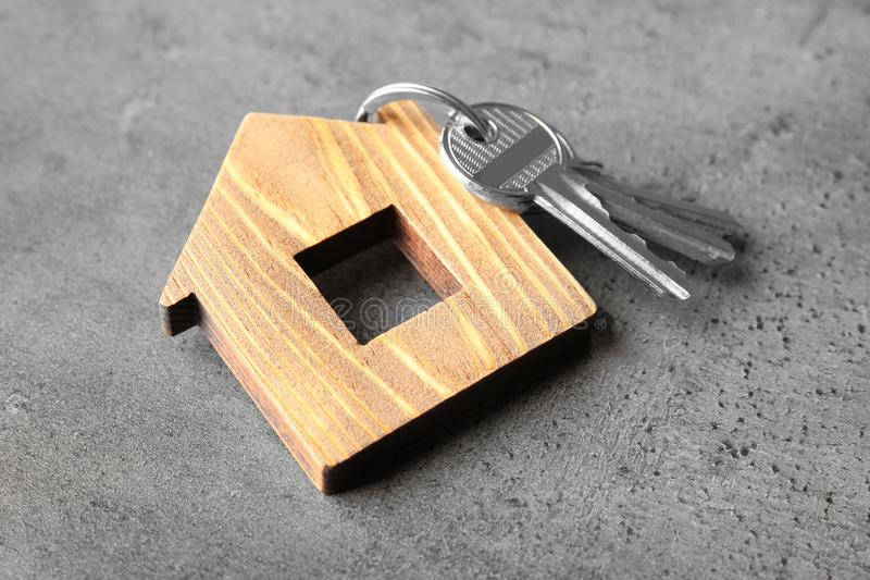 Bunch of keys and house model on grey. Background stock image
