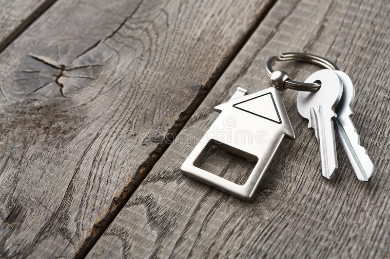 Bunch of keys with house shaped keychain on rustic wood stock photography