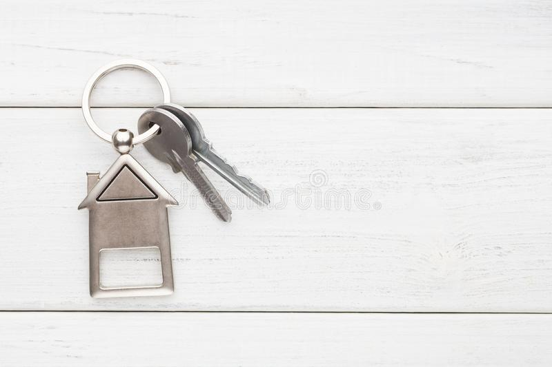 Bunch of keys with house shaped keychain on white wood. Two steel keys with house shaped trinklet on keyring on white wooden background with copy space. Home key stock photo