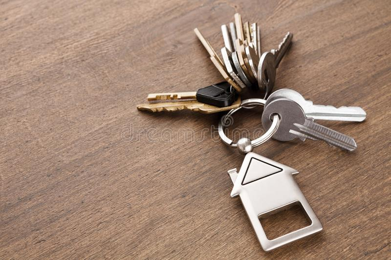 Bunch of keys with house shaped keychain on white wood. Bunch of keys on a house shaped keychain at wooden table background. Concept for real estate or renting stock photography