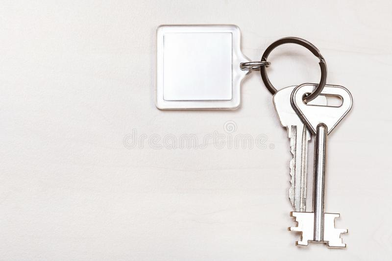 Bunch of keys on keyring with blank white keychain. On pale brown table stock image