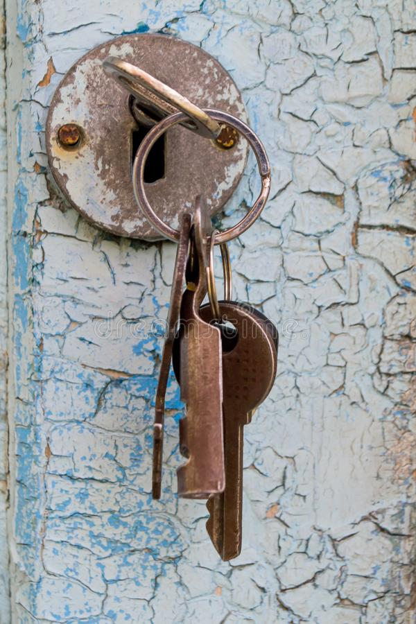 Bunch of keys. A bunch of keys sticking out of the door lock, real, estate, house, background, home, table, concept, space, security, access, rustic, copy, metal royalty free stock photo