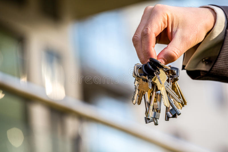 Bunch of keys to your brand new apartment. Bunch of keys in hand of elegant man stock photo