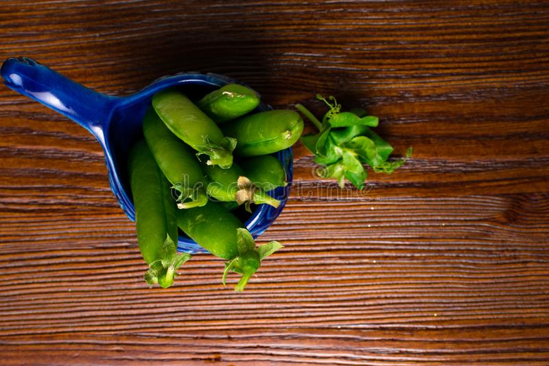 Fresh, young green peas in blue bowl on the old wooden background. Bio healthy food. Selective focus. Copy space background royalty free stock image