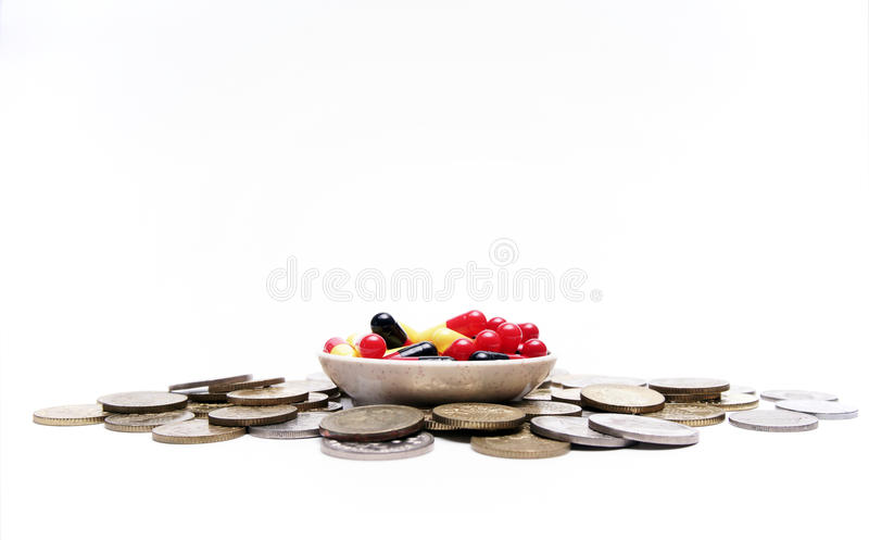 A bunch of medical capsule in a small bow and coins at the side. stock images