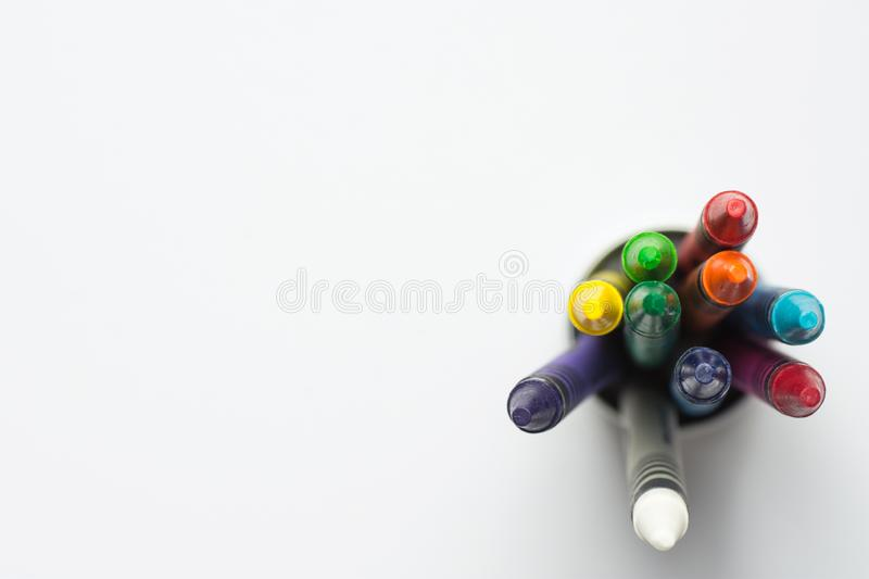 Bunch of Multicolored Wax Crayons Pencils in Cup. Top View White Background. Education Arts Crafts Creativity Concept stock photography