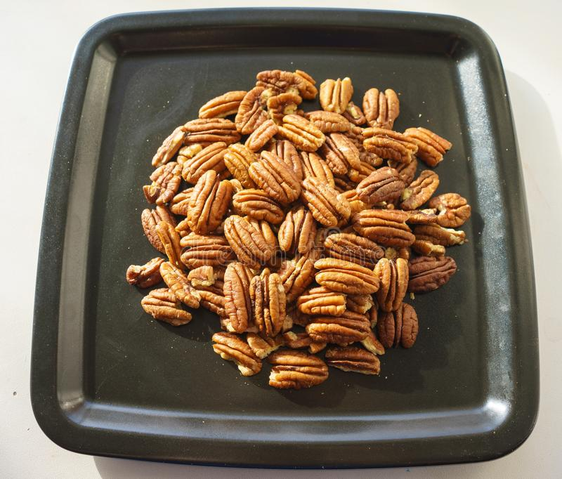 A bunch of nuts pecan on a black plate. Close-up photo vector illustration
