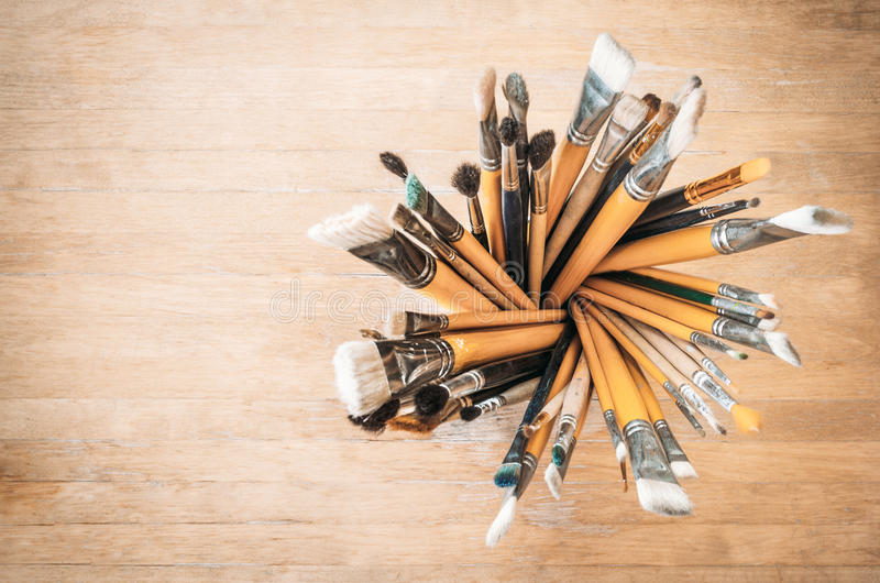 Bunch of old artist paintbrushes in glass on wooden rustic table with space for text stock photos
