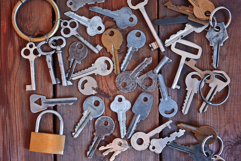 A bunch of old keys on a wooden table. A bunch of old keys and lock on a wooden table royalty free stock photography