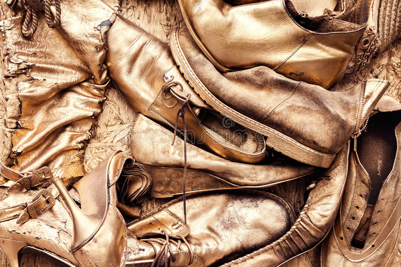 Bunch of old shoes and boots painted in golden yellow stock photos