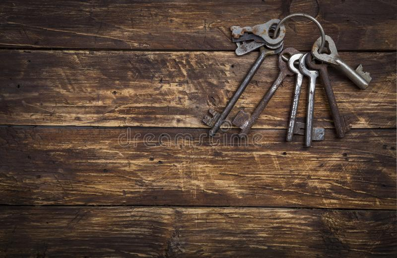 Bunch of old vintage keys on wooden background, top view with space for text. Safety and security concept, copy space stock photography