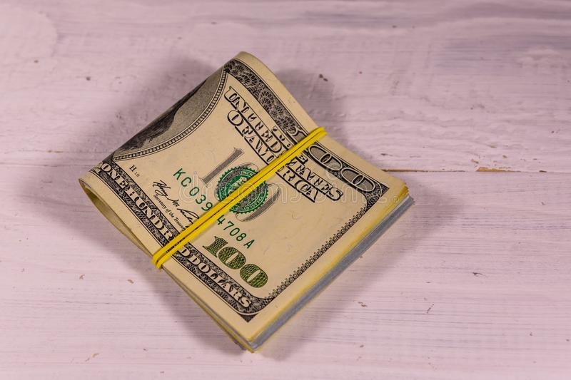 Bunch of the one hundred dollar bills with rubber on wooden table royalty free stock image