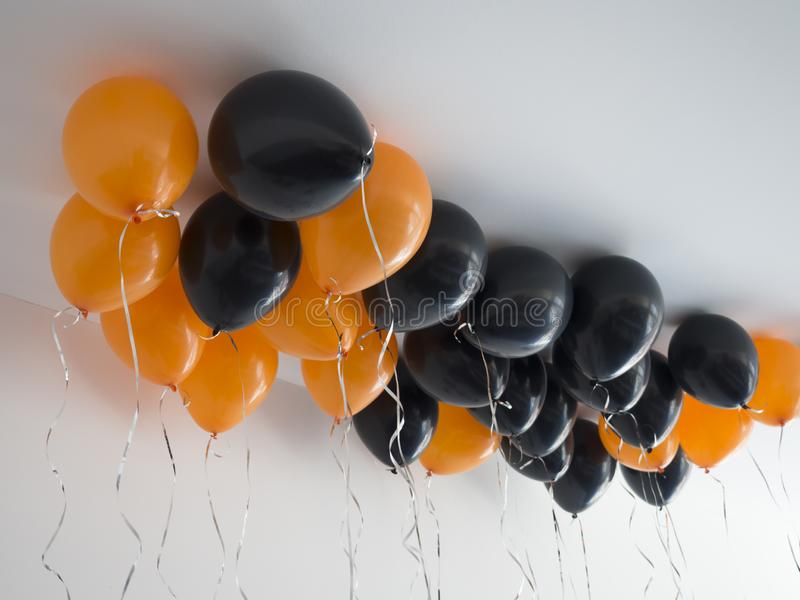 Bunch of orange and black air balloons for halloween or birthday over white ceiling background. Holidays, decoration and royalty free stock photography