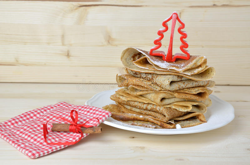 Bunch of pancakes and Christmas decoration. Bunch of buckwheat pancakes with powdered sugar and decorated with Christmas decoration stock image