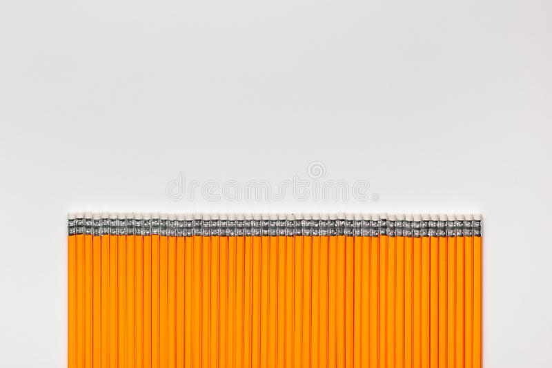 A bunch of pencils aligned in a straight line on white background stock photos