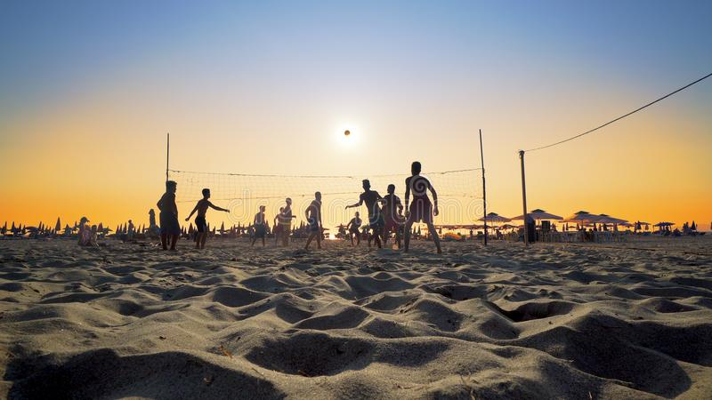 Bunch of people play beach volleyball at Beach stock photo