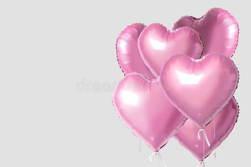 Bunch of pink color heart shaped foil balloons isolated on bright background. Minimal love concept royalty free illustration