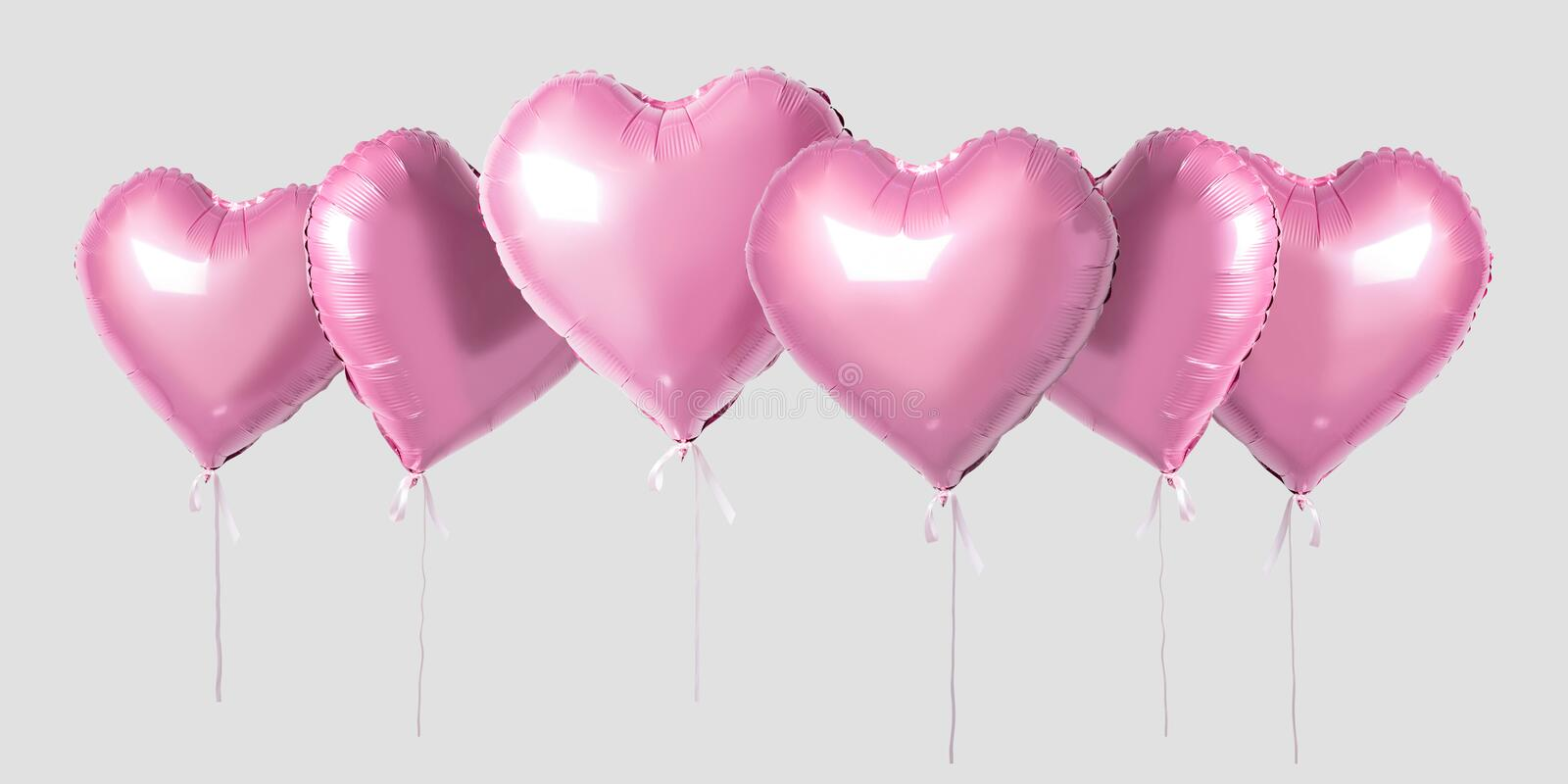 Bunch of pink color heart shaped foil balloons isolated on bright background. Minimal love concept.  royalty free stock image
