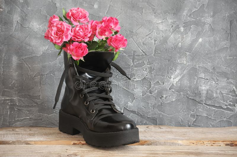 Bunch of pink roses in black combat boot. Bunch of pink rose flowers in black combat boot on wood against grey plaster wall royalty free stock photo