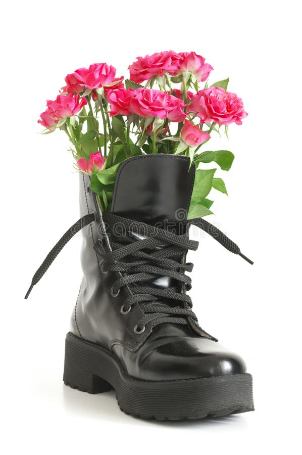 Bunch of pink roses in black combat boot. Bunch of pink rose flowers in black combat boot isolated on white background royalty free stock photography