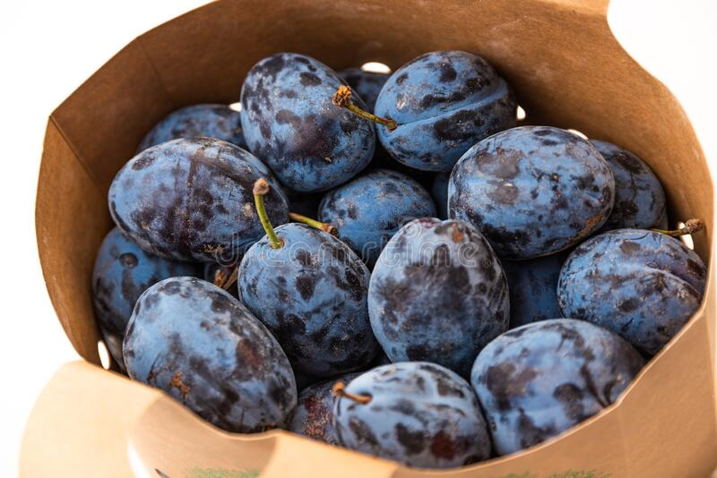 Bunch of plums in paper bag from supermarket. Fruit theme royalty free stock image
