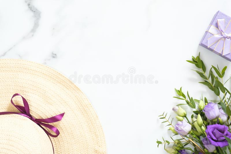 Bunch of purple rose flowers, straw hat, gift box on marble background. Flat lay, top view, overhead royalty free stock photography