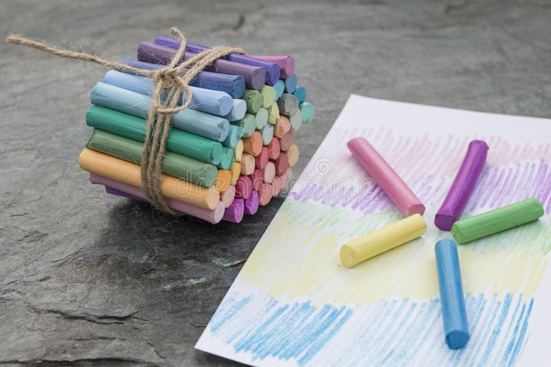 Bunch of rainbow colored pastel crayons on black backround royalty free stock photography