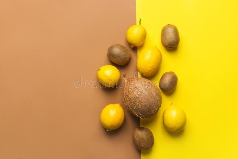 Bunch of raw organic lemons kiwi coconut on duotone yellow brown background. Creative flat lay food poster. Vegan vitamins summer. Tropical fruits cocktail stock photo