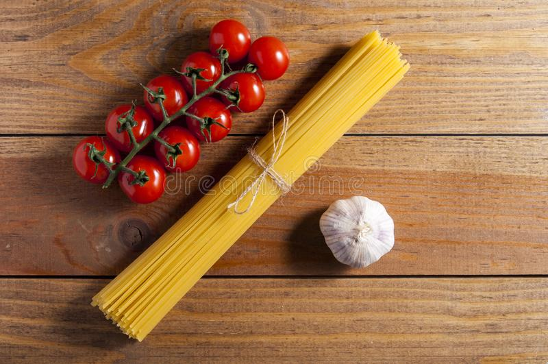Bunch of raw spaghetti tied with rope, tomatoes cherry and bulb of garlic on brown wooden background stock photography