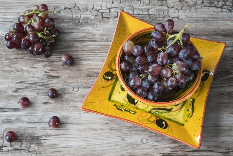 Bunch of red grapes in orange bowl, against wooden background stock photos