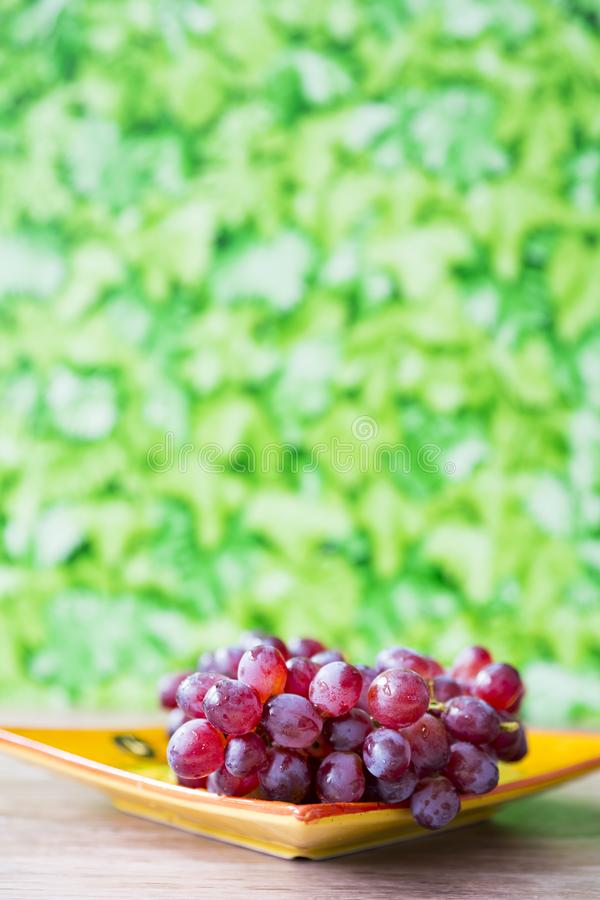 Bunch of red grapes on yellow orange plate, against green blur background stock image