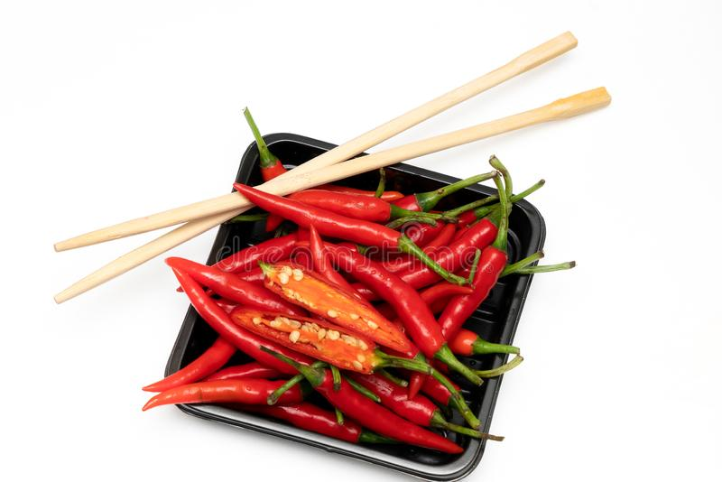 A bunch of red hot chili peppers on a black plate with Chinese sticks on a white background royalty free stock image