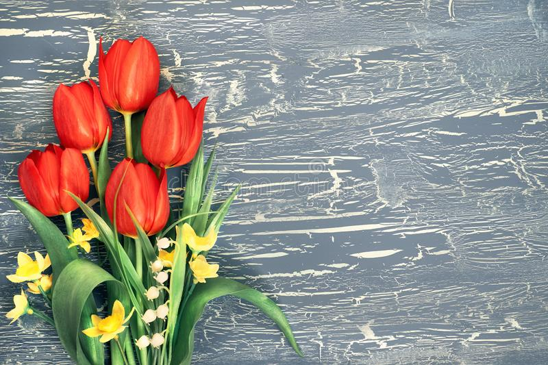 Bunch of red tulips on rustic background, space. Bunch of red tulips, daffodils and lily of the valley flowers on rustic background. Space for your test, flat royalty free stock photography