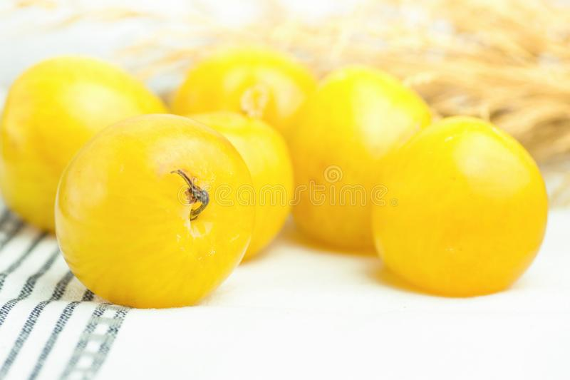 Bunch of ripe juicy organic yellow plums bouquet of dry autumn plants flowers on white cotton towel. Autumn fall Produce stock images