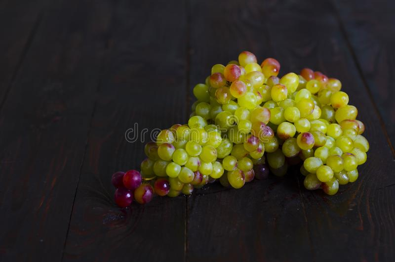 Bunch of ripe juicy sweet raisins grapes on a dark wooden background. low key. copy space, mock up. Text royalty free stock photos