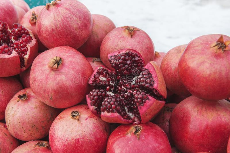 A bunch of ripe red pomegranates on the street in winter. One of the fruits is cut in half. Visible grains and bones stock photos