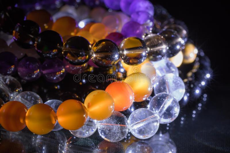 Bunch of semiprecious gemstone bracelets on black background - cornelian, amethyst, quartz royalty free stock photography