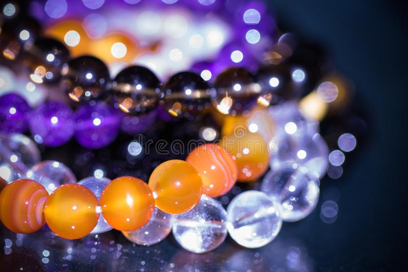 Bunch of semiprecious gemstone bracelets on black background - cornelian, amethyst, quartz royalty free stock photos