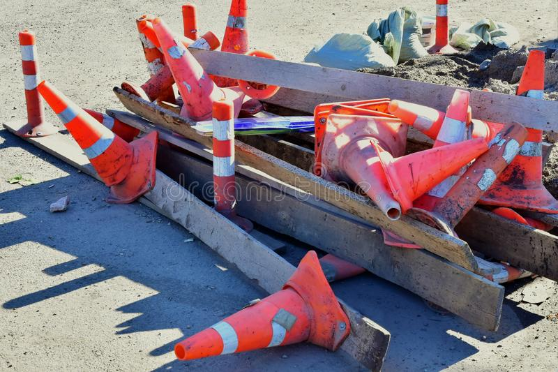 A bunch of signal posts and cones are lying on the road. Waste after road repair. The trash left by road service builders stock photo