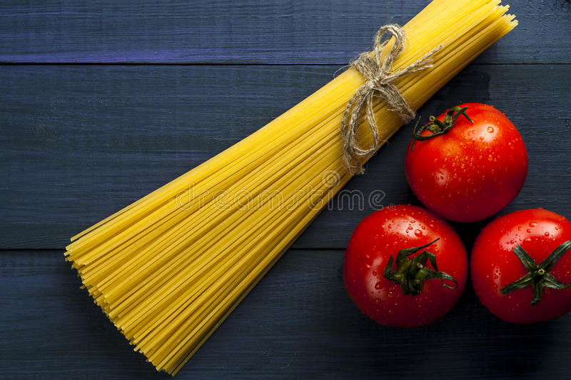 Bunch of spaghetti and three tomatoes stock photography