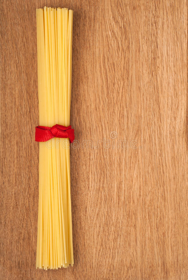 Bunch of spaghetti tied up with a red ribbon royalty free stock photography