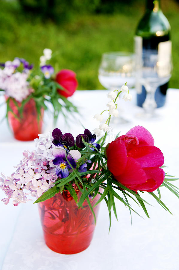 A bunch of summer flowers for picnic. A bouquet of different multicolor summer flowers - pansy, lilac, lily-of-the-valley, peony - in a red glass, arranged for royalty free stock image