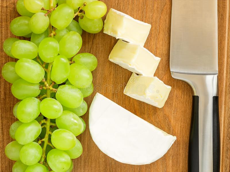 Bunch of sweet green grapes, pieces of tasty cheese camembert and chef knife on a brown wooden cutting board. Soft cheese covered. With edible white mold. Top royalty free stock photography