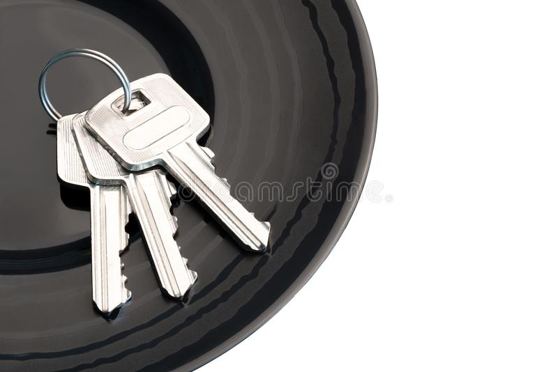 Bunch of three keys in black saucer. Isolated white background stock photo